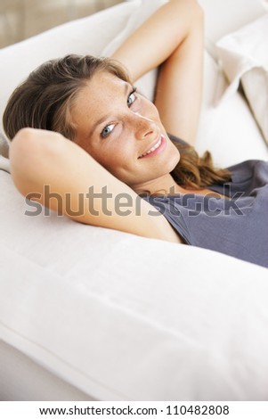 Closeup of a smiling young woman lying on couch - stock photo