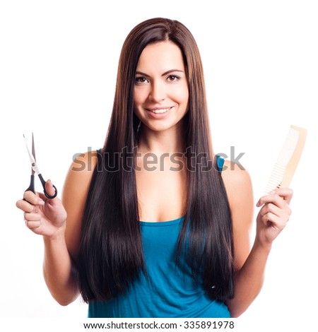 Closeup of a smiling young woman with beautiful hair, holding a pair of scissors in one hand and a comb in the other