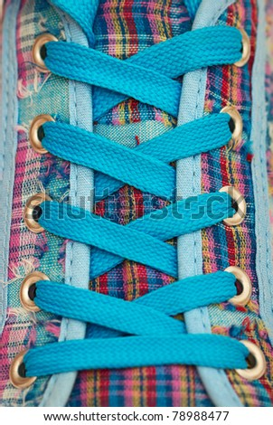 Closeup of a sneaker with blue shoelaces, abstract background - stock photo