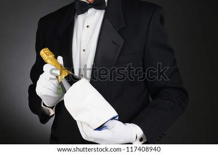 Closeup of a Sommelier holding a Champagne bottle in front of his torso. Man is unrecognizable. Horizontal format on a light to dark gray background. - stock photo