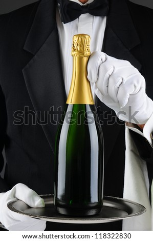 Closeup of a sommelier holding a champagne bottle on a serving tray in front of his torso. Man is wearing a tuxedo and is unrecognizable. Vertical Format. - stock photo