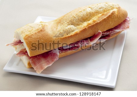 closeup of a spanish serrano ham sandwich served in a plate