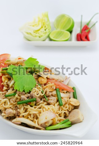 Closeup of a spicy Thai noodle with pork and fresh vegetables.