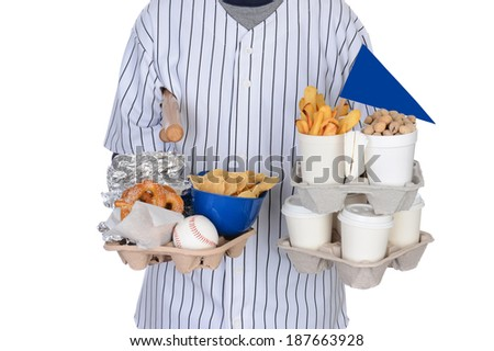 Closeup of a sports fan carrying souvenirs and food trays in both hands. Food tray had hot dogs, peanut,s pretzels, chips and french fries. Souvenirs include pennant, baseball, mini bats and helmet. - stock photo