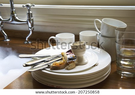 Closeup of a stack of dirty dishes and silverware by sink in the kitchen - stock photo
