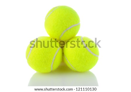 Closeup of a stack of tennis balls on a white background with reflection. - stock photo