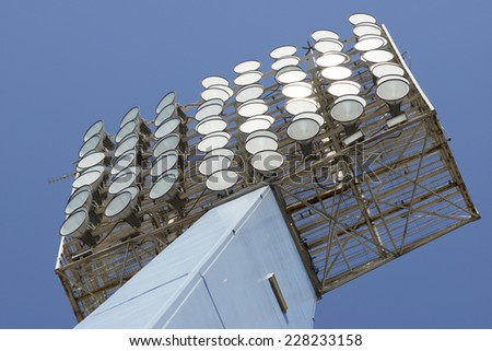Closeup of a stadium lights with blue sky. - stock photo