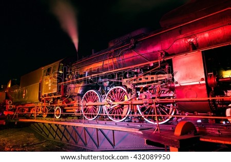 closeup of a steam train locomotive at night