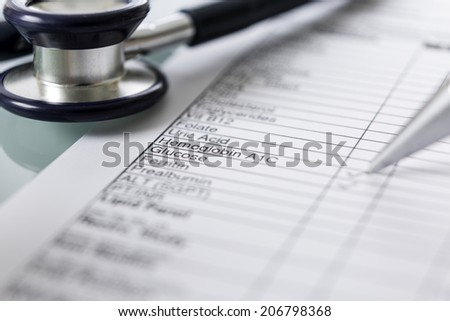 closeup of a stethoscope and a blood analytic form - focus on hemoglobin and glucose words - stock photo