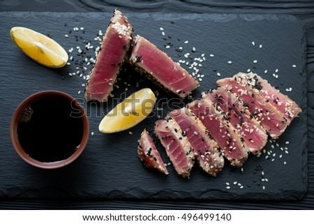 Closeup of a stone slate tray with sliced roasted tuna fillet, top view