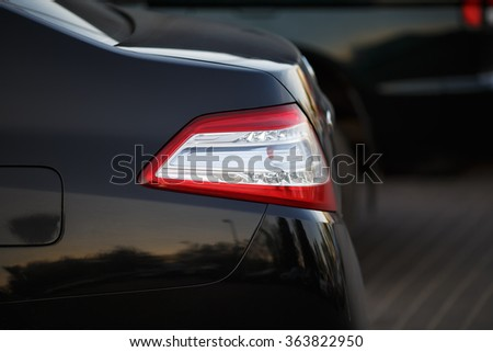 Closeup of a taillight on a modern black car with reflection. Shallow depth of field. Selective focus. - stock photo