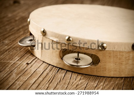 closeup of a tambourine on a rustic wooden table, heavy processing for retro bleached look - stock photo