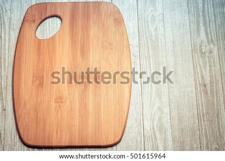 Closeup of a tan wooden cutting board set on gray weathered boards
