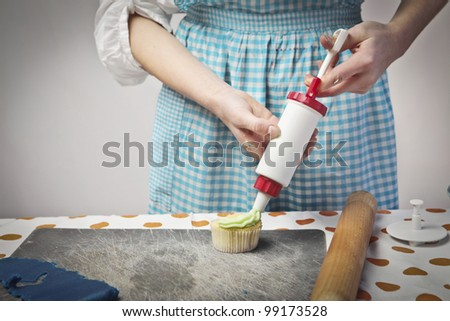 Closeup of a teenage cook garnishing a cupcake with some whipped cream - stock photo