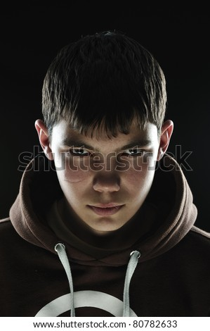 Closeup of a teenager with his hood down looking menacing - stock photo