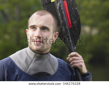 Closeup of a thoughtful young man with kayak paddle against blurred trees - stock photo