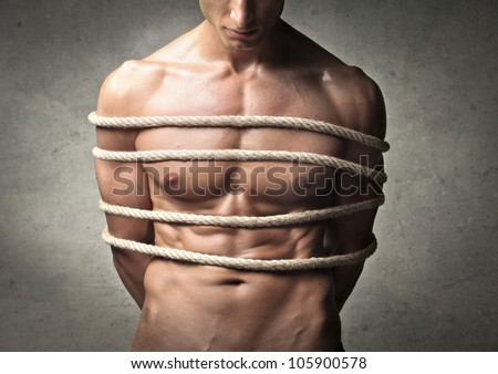 Closeup of a tied bare-chested young man's chest - stock photo