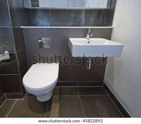 closeup of a toilet and sink of a modern bathroom - stock photo