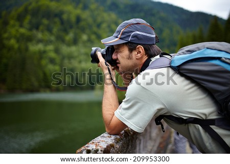 Closeup of a tourist taking photos of a lake in the mountains - stock photo