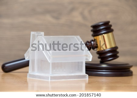 Closeup of a toy house model and a brown gavel  - stock photo