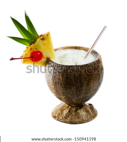 closeup of a tropical coconut drink garnished with a pineapple slice with leaves and a cherry - stock photo