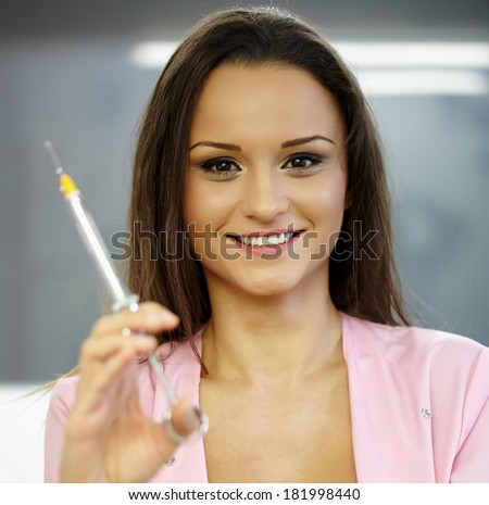 Closeup of a very beautiful woman doctor holding a syringe, ready for shot - stock photo