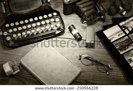 Closeup of a vintage photography still life with typewriter, folding camera, loupe, roll film, flash bulbs, contact prints and book on a wood table. Black and white toned image for a vintage feel.  - stock photo