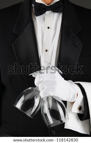 Closeup of a waiter in a tuxedo holding two wineglasses in front of his body. Man is unrecognizable. - stock photo