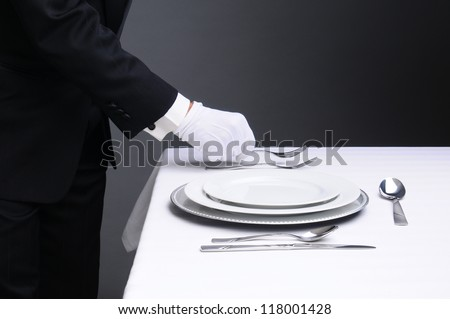 Closeup of a waiter in a tuxedo setting a formal dinner table. Horizontal format on a light to dark gray background. Man is unrecognizable. - stock photo