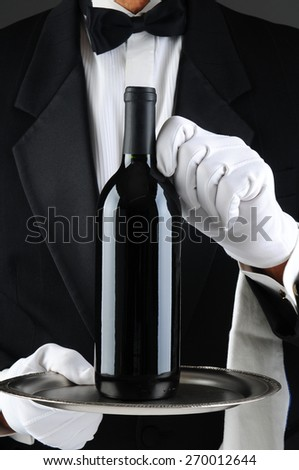 Closeup of a waiter wearing a tuxedo and white gloves holding a wine bottle on a serving tray. Vertical format. The man is unrecognizable. - stock photo