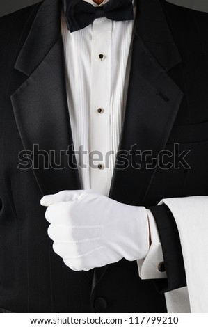 Closeup of a waiter wearing a tuxedo and white gloves. Man is unrecognizable and holding his lapel. - stock photo