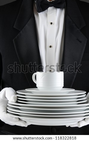 Closeup of a waiter wearing a tuxedo carrying a stack of plates. Vertical format, man is unrecognizable. - stock photo