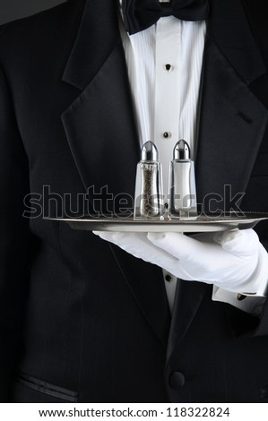 Closeup of a Waiter wearing a tuxedo holding a serving tray with salt and pepper shakers. Vertical format, man is unrecognizable.