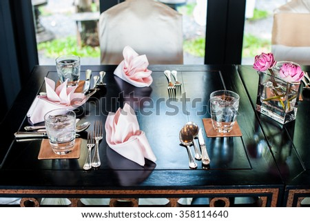 Closeup of a wedding table place setting with colorful centerpiece made up of sliced oranges in a vase. - stock photo