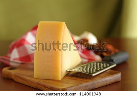 Closeup of a wedge of parmesan cheese on a wooden board. - stock photo