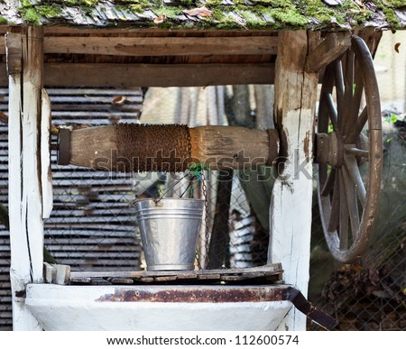 Closeup of a well with wheel, pulley and aluminum bucket - stock photo