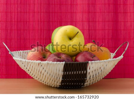 Closeup of a white basket full of red, yellow, green apples on a wooden surface in front of the magenta background