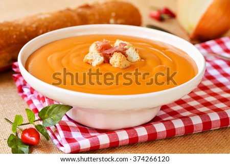 closeup of a white ceramic bowl with salmorejo cordobes, a typical spanish tomato soup similar to the gazpacho, topped with serrano ham and croutons, on a set table - stock photo