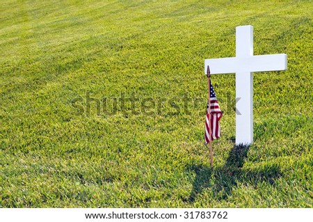 Closeup of a white cross and an American flag on Memorial Day against light green grass, with copyspace on left - stock photo