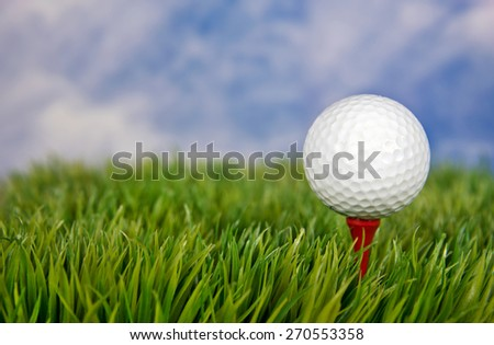 Closeup of a white golf ball on a red tee in grass - stock photo