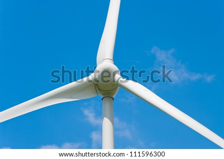closeup of a wind turbine against a blue sky - stock photo
