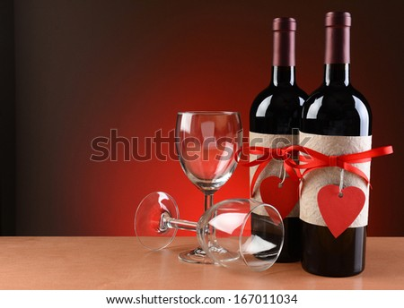 Closeup of a wine bottles decorated for Valentines Day. Two empty wineglasses are next to the bottles with one on its side.  Both bottles have a red ribbon and heart shaped tag and a blank label. - stock photo