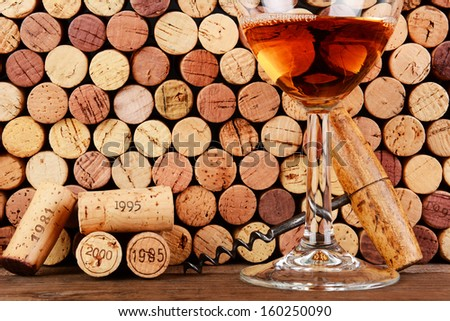 Closeup of a wineglass in front of a wall of used corks. An antique cork screw and dated corks are adjacent to the glass. Horizontal format filling the frame. - stock photo