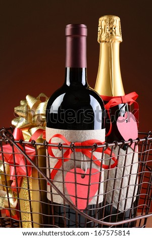 Closeup of a wire shopping basket with Valentines Presents. Vertical Format on a light to dark red background. Items include champagne, wine, gift boxes. The bottles have heart shaped gift tags. - stock photo