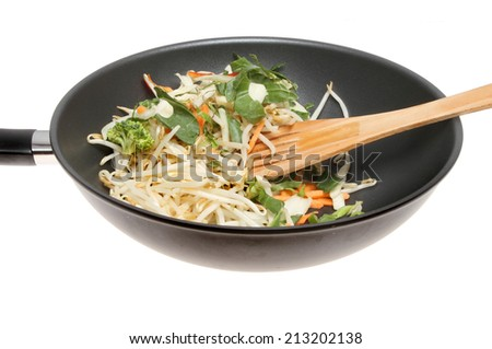 Closeup of a wok with stir fry vegetables, bean sprouts and a wooden spatula isolated against white - stock photo