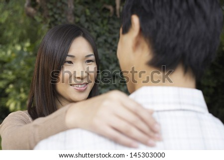 Closeup of a woman and man outside looking at each other - stock photo