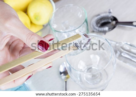closeup of a woman hand filling a glass with ice from an ice bucket with a bamboo ice tongs on a gin tonic preparation session - focus on the ice cube - stock photo