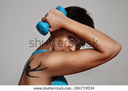 closeup of a woman making an exercises with a dumbbells