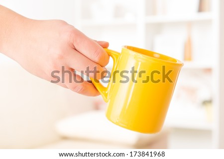Closeup of a woman's hand holding a mug of drink