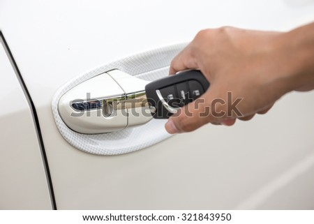Closeup of a woman's hand inserting a key into the door lock of a white car.(focus keyhole)